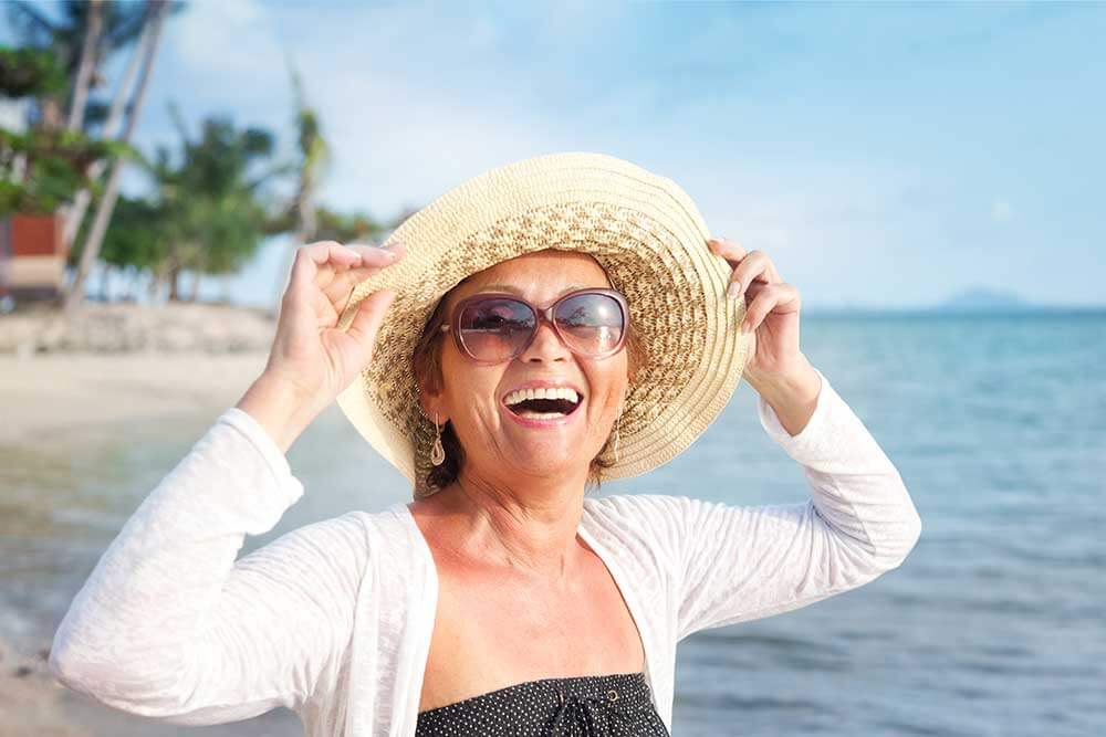 Older woman walking on the beach wearing a hat and smiling..